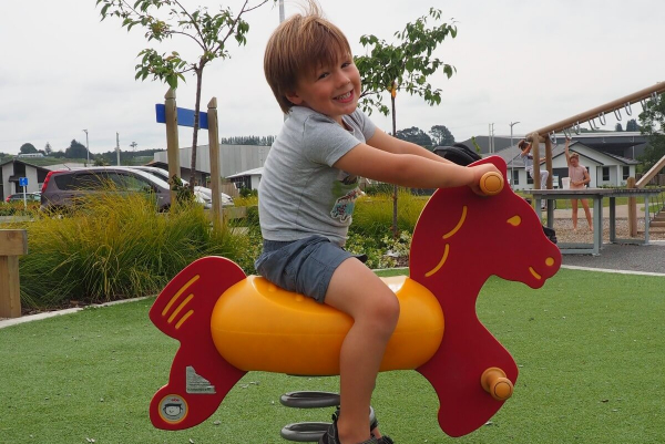Boy on a rocking horse at The Lakes Tauranga